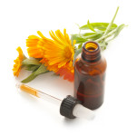 Calendula flowers, open glass bottle and pipette with tincture on white background.
